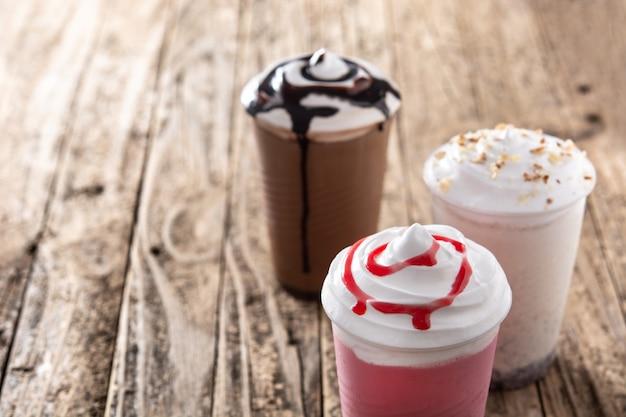 Клубника, шоколад и белые молочные коктейли со льдом на деревянном столе