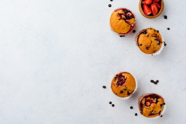 Strawberry chocolate cupcakes muffins on concrete white surface