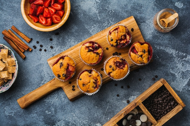 Strawberry chocolate cupcakes muffins on old wooden stand on concrete gray surface