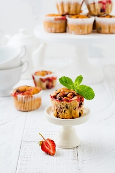 Strawberry chocolate cupcakes muffins on white ceramic stand on light surface