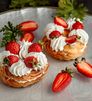 Strawberry choux pastry topped with white cream and strawberries