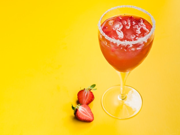 Strawberry cocktail with ice cubes in glass with sugared rim