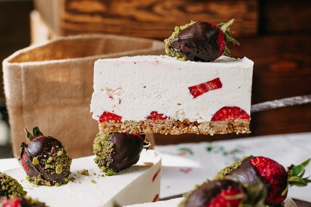 Strawberry cream cake getting sliced by cook yumy delicious sweet cake inside kitchen