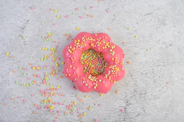 Клубничный пончик украшен глазурью и обсыпкой на полу