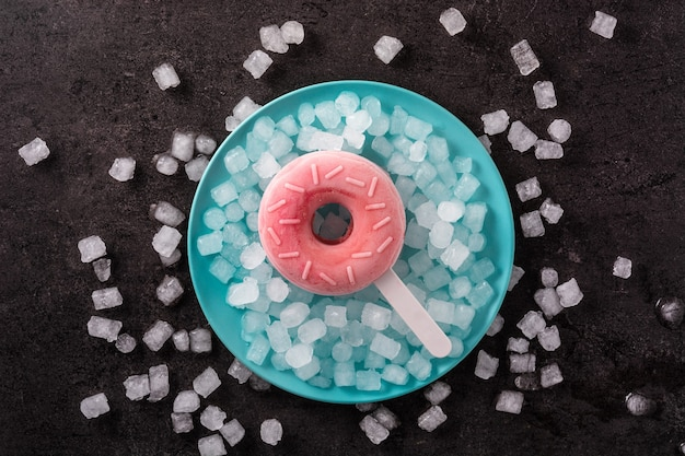 いちごドーナツアイスキャンディーと黒い背景の砕いた氷