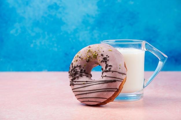 Клубничный пончик с украшениями и стакан молока на розовом столе.