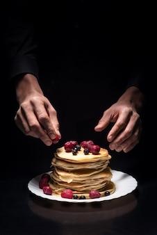 いちごの夢。ベリーを使用し、レストランで料理をしながら、パンカケを飾る男の手のクローズアップ。