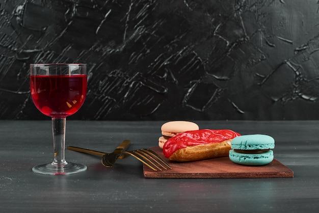 Eclair alla fragola con macarons francesi e un bicchiere di vino.