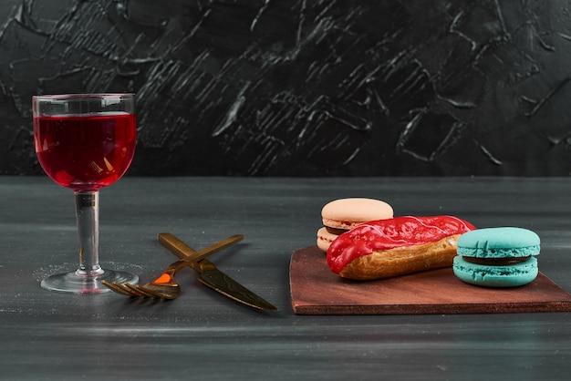 Eclair alla fragola con un bicchiere di vino e macarons.