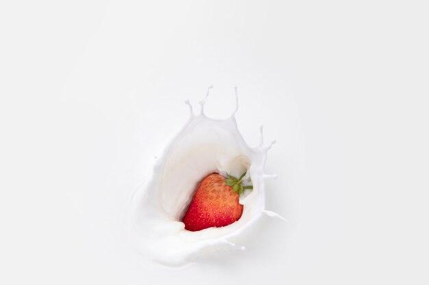 Клубника падает в белое молоко