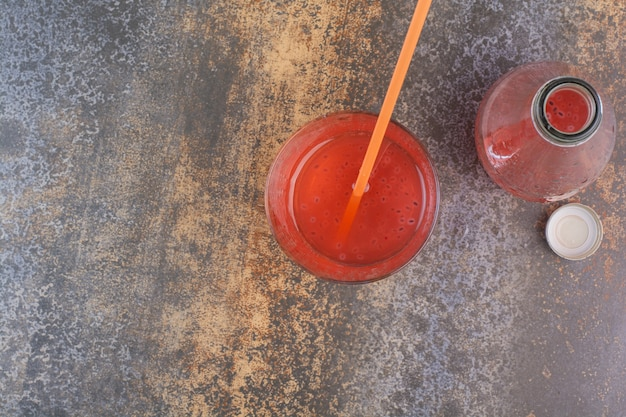 大理石の表面にストローとボトルのイチゴフレッシュジュース