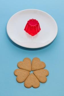 ハート型のクッキーと白い皿にイチゴゼラチン