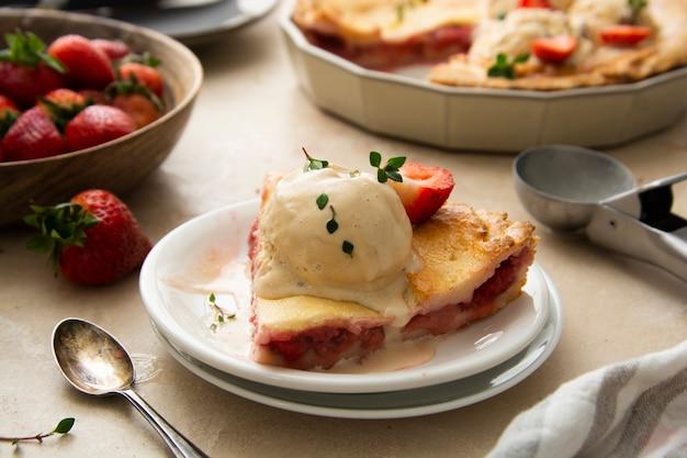 イチゴ、新鮮なイチゴで満たされたグルテンフリーのパイ、アイスクリームスクープを添えて、上面図。夏の食べ物。