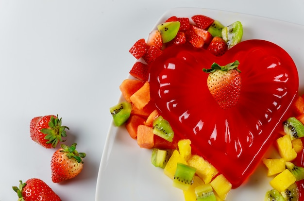 Strawberry heart shape gelatin with fruits on white plate