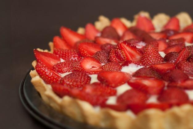 Strawberry homemade tart over dark background.