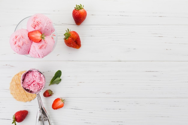 Strawberry ice cream in bowl on wooden surface