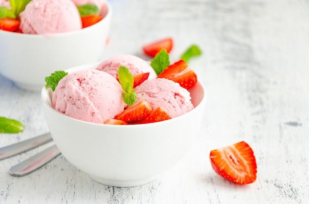 Клубничное мороженое в миске со свежей клубникой и мятой на деревянном фоне. скопируйте пространство.