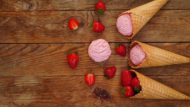 와플콘에 딸기 아이스크림. 나무 배경에 빨간 열매와 아이스크림 공. 위에서 보기