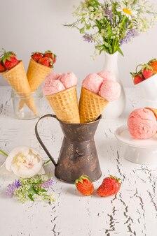 白い木製の背景にワッフルカップのイチゴアイスクリーム