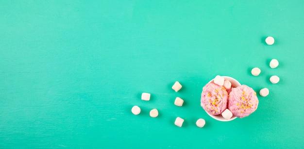 アクアマリンの背景にトッピングと白いボウルにストロベリーアイスクリームスクープ