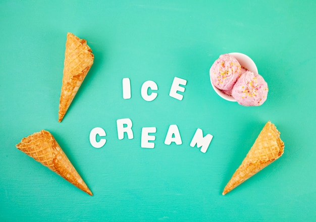 Strawberry ice cream  scoops in white bowl with topping on aquamarine background