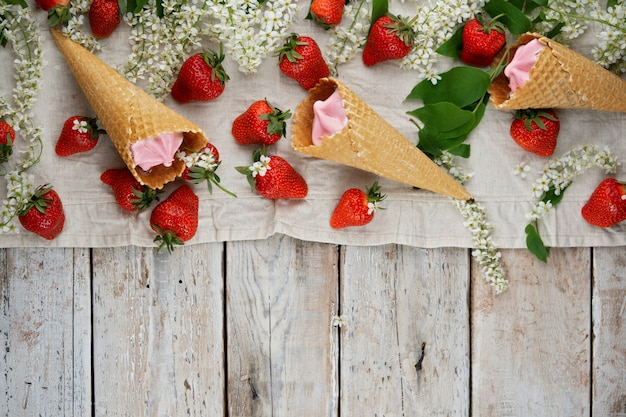 Strawberry ice cream in waffle cones surrounded