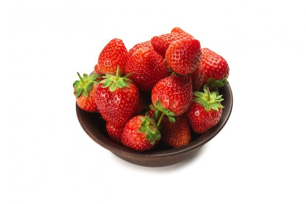 Клубника в керамической коричневой миске. макрос свежих ягод. изолированные на белом.
