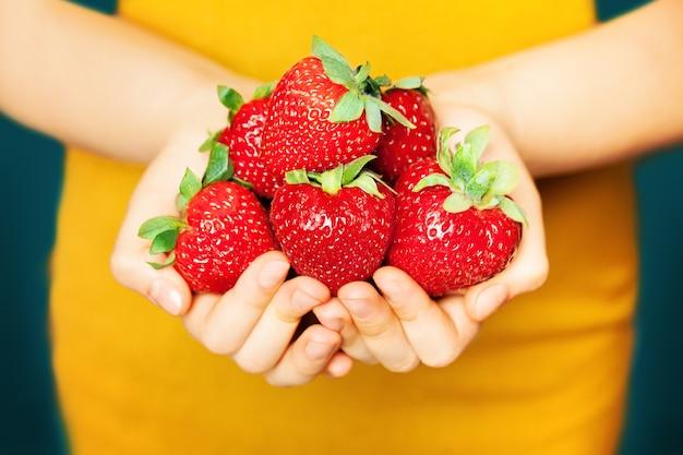 여성의 손에 딸기입니다. 노란색 바탕에 빨간 열매입니다. 건강한 식생활 개념