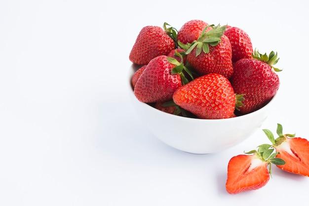 흰색 배경에 흰색 그릇에 딸기. 확대.