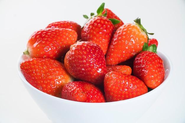 흰색 테이블에 흰 그릇에 딸기 프리미엄 사진