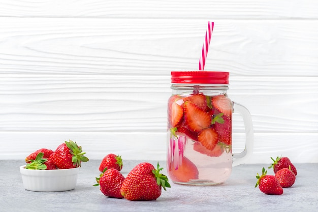 Strawberry infused water, cocktail, lemonade or tea. summer iced cold drink with strawberry, lemon and leaf of mint on white wooden background. flat lay