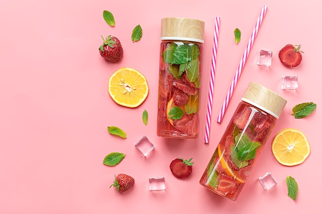 Strawberry infused water, summer iced drink with strawberry, lemon and leaf of mint on pink background