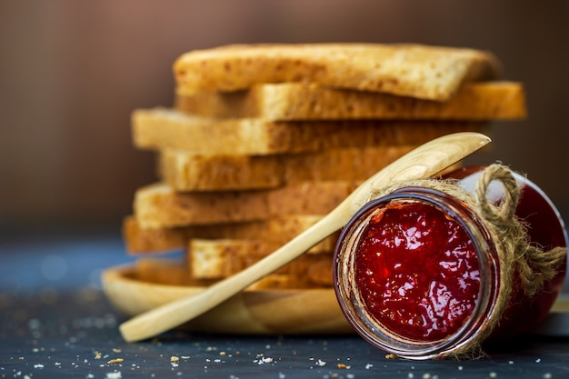 Strawberry jam bottle and whole wheat bread are stacked on table.