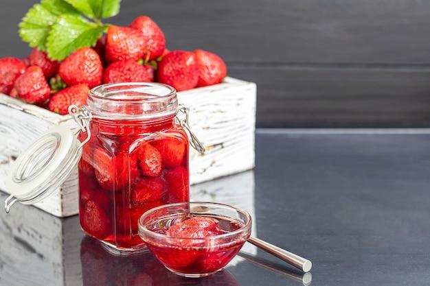 新鮮なイチゴの横にあるガラスの瓶にいちごジャム