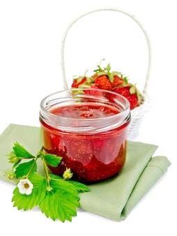 ガラスの瓶にイチゴジャム、白い背景で隔離のナプキンに白い籐のバスケットにイチゴ