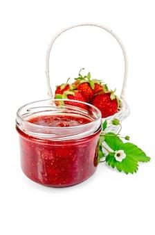 白い籐のバスケットにイチゴ、イチゴの葉と白い背景で隔離の花とガラスの瓶にイチゴジャム