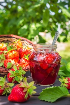 Strawberry jam and juicy ripe strawberries on a wooden table in the garden on a summer sun
