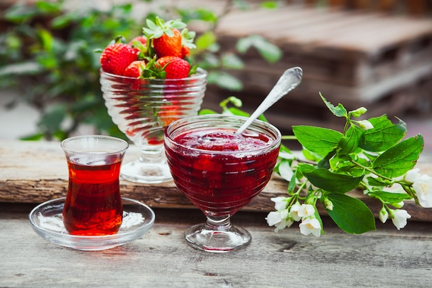Strawberry jam in a plate with spoon, tea in glass, strawberries, plant side view on wooden and yard table