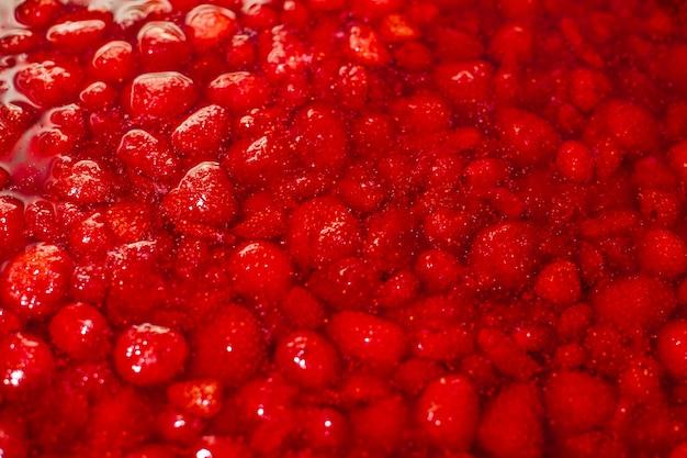 Клубничное варенье, красные ягоды в сиропе крупным планом в медном тазе