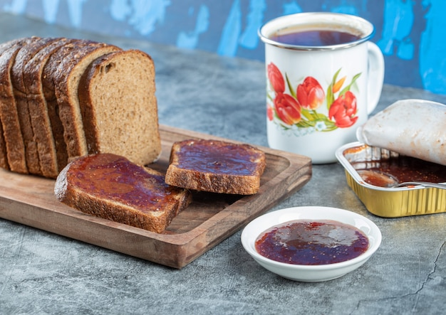 Strawberry jam with slice of brown bread and cup of tea.