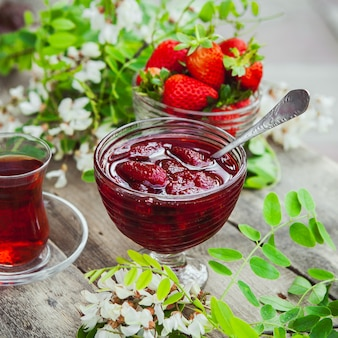Strawberry jam with spoon, a glass of tea, strawberries, plant in a plate on wooden and pavement table, close-up.