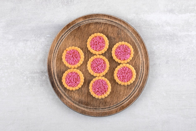 Strawberry jelly biscuits on a board, on the marble table.