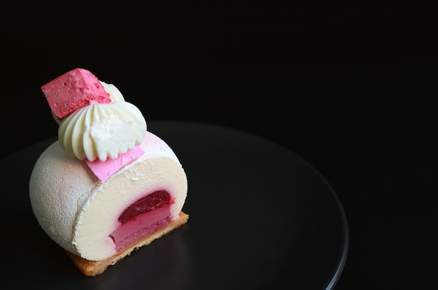 Strawberry jelly vanilla mousse cake on black plate with copy space on black background