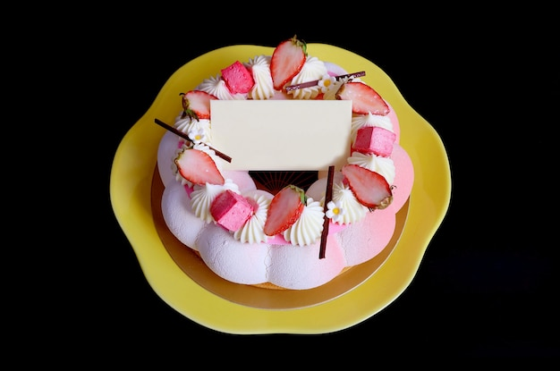 Strawberry jelly vanilla mousse cake with blank white chocolate greeting card on black