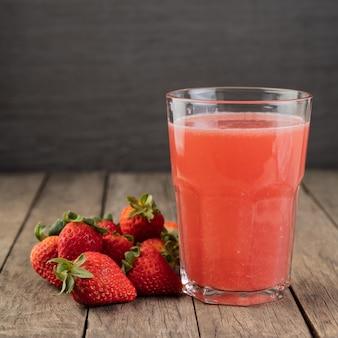 木製のテーブルの上にフルーツとグラスのイチゴジュース。