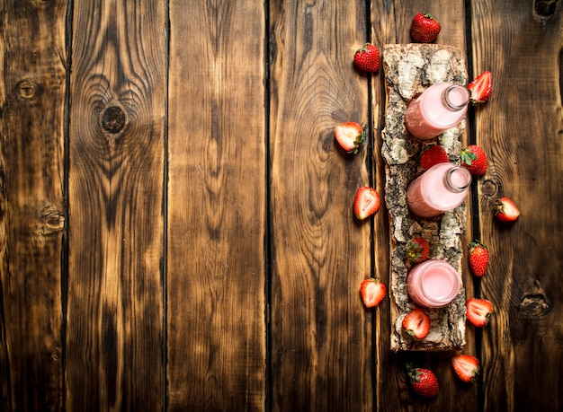 白樺のトレイにイチゴジュース。木製のテーブルの上。