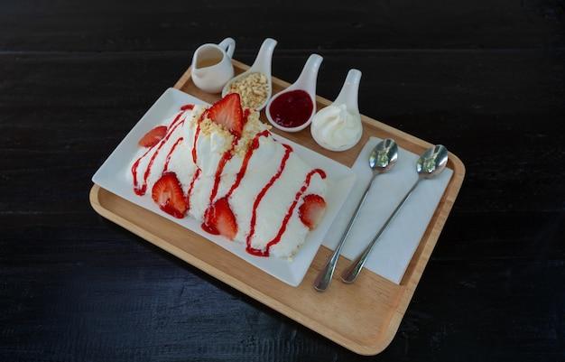 いちごかき氷(かき氷デザートミルクフレーバー)またはピンス(韓国デザート)は、白いプレートにいちごソースとトッピングをテーブルに添えて、甘い食べ物を提供します