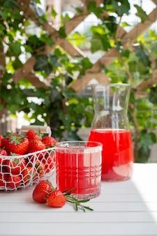 白い木製のテーブルの上に、イチゴのレモネード、熟したベリーとローズマリーの赤い飲み物。夏のさわやかなドリンク。