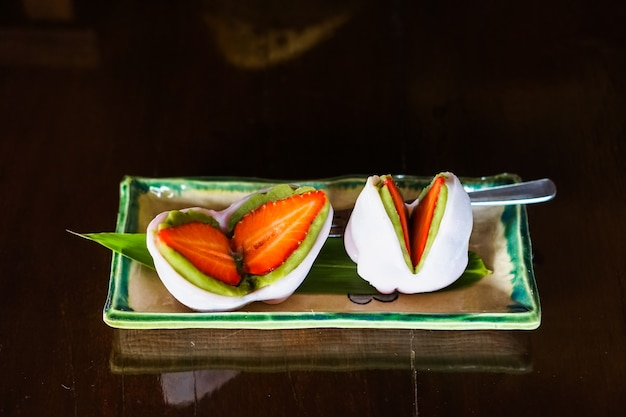 Strawberry and matcha mochi in a plate.