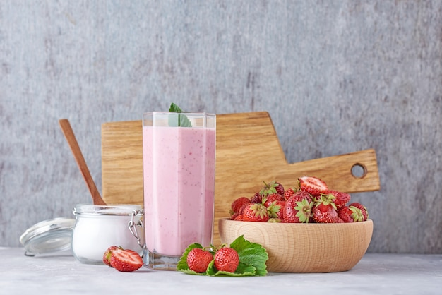 Strawberry milk shake in a glass jar and fresh strawberries with leaves